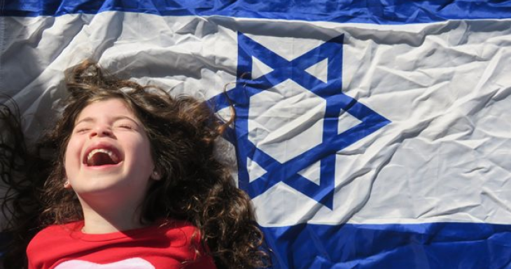 Child smiling next to Israeli flag