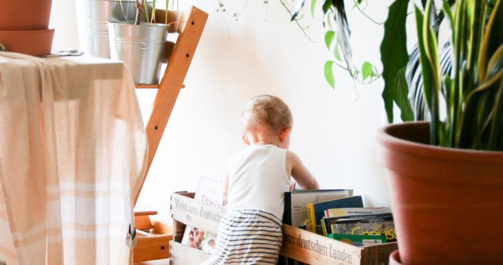 A toddler digs into a container of books