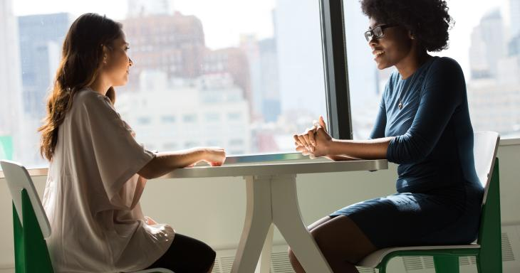 Two women at table talking