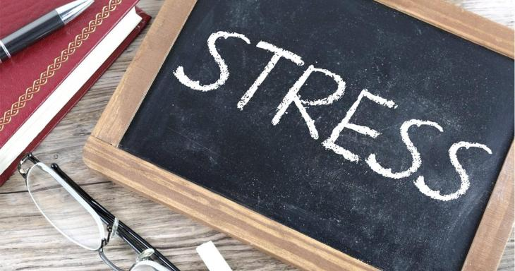 Stress written on chalk board in all caps, with a notebook, pencil, and reading glasses