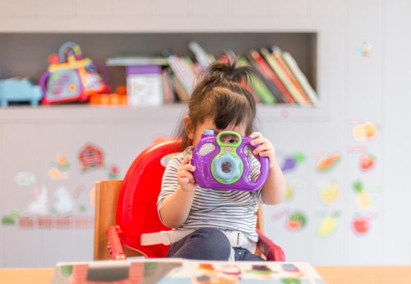 Preschool child looking through toy camera