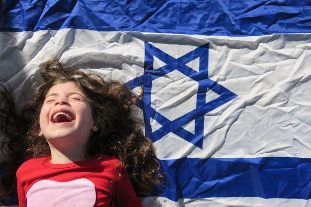 Child smiling next to Israeli flag