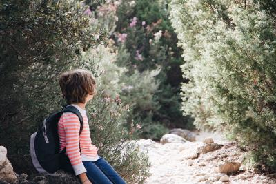 Child out in a natural setting with a school backpack on.