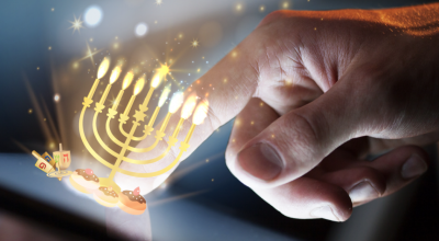 A hand tapping a virtual menorah sitting on a smart device